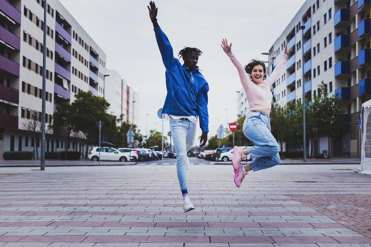 Full length of man jumping in city
