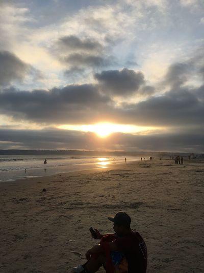 The sun powering through a wall of fluffy clouds. Gray day at Coronado Island Beach