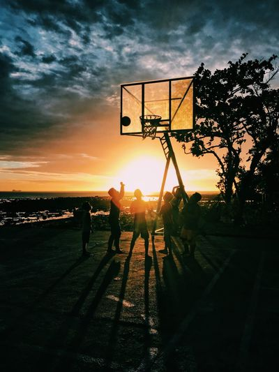Silhouette People Playing Basketball Against Sky During Sunset