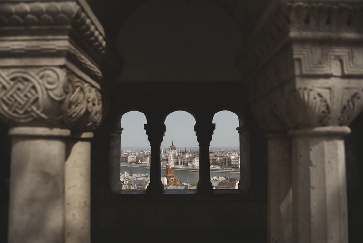 Different point view of the hungarian parliament building from a window of fishermen's bastion in buda Arch Architectural Column Architecture Building Building Exterior Built Structure City Day History No People Old Ornate Outdoors The Past Tourism Travel Travel Destinations Window