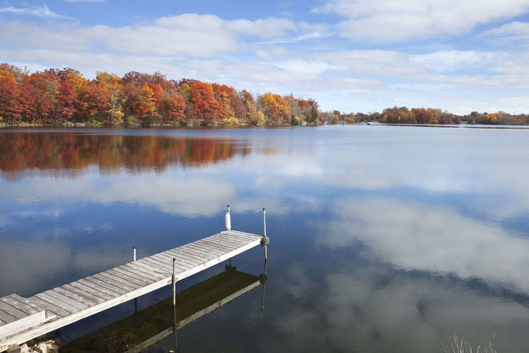 Minnesota lake and dock near trees in autumn color under blue sky and clouds Landscape Autumn MidWest Minnesota Pier Red USA Beauty In Nature Blue Cloud - Sky Color Day Dock Fall Lake Maple No People Oak Orange Color Outdoors Reflection Sky Tranquility Tree Water