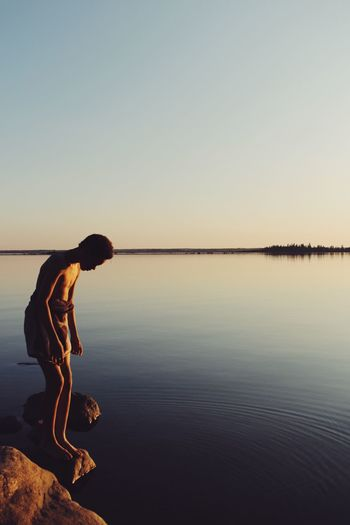 Shirtless teenage boy standing in lake against clear sky during sunset
