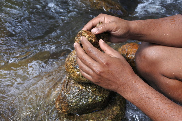 Midsection of man stacking stones by river