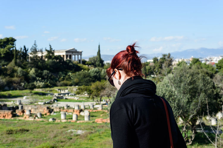 View of an ancient Greek temple in the Agora over red haired girl's shoulder Agora Ancient Civilization Athens Athens, Greece Casual Clothing City Day Focus On Foreground Greece Hat Leisure Activity Lifestyles Mountain Nature Outdoors Portrait Red Hair Sky Sunny Tourism Tourism Greece Travel Destinations Tree Vacation