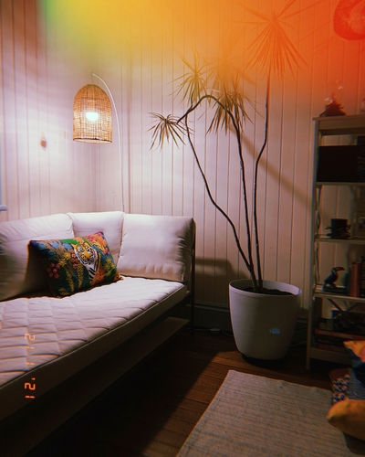 Illuminated electric lamp on bed against wall at home