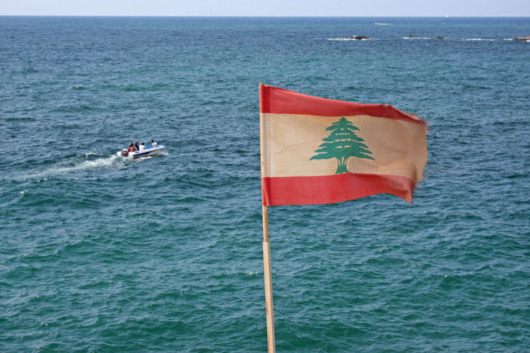 Scenic view of flag on sea against sky