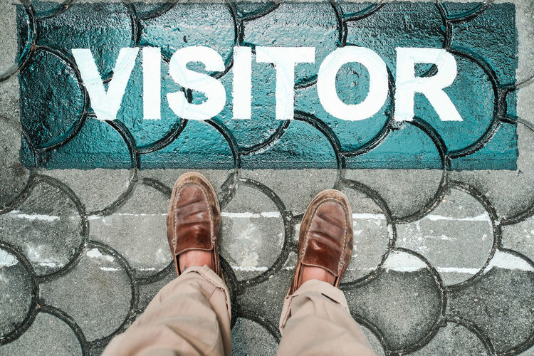 Visitor On Earth Leather Signage Capital Letter Communication Footpath High Angle View Human Foot Human Leg Leisure Activity Lifestyles Low Section One Person Outdoors Parking Paving Stone Personal Perspective Shoe Standing Street Text
