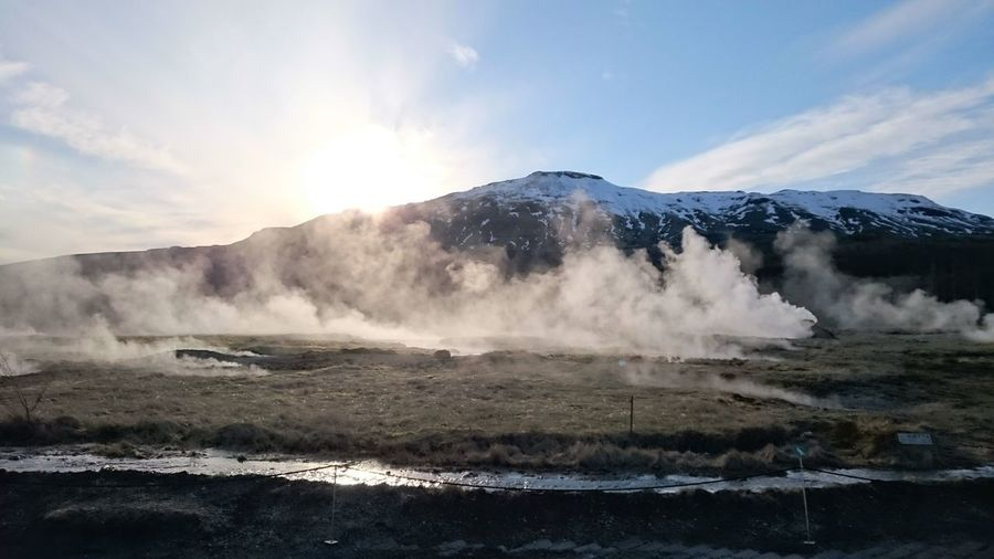 Scenic view of geyser against mountains and sky