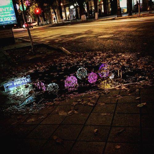 Close-up of wet illuminated street during rainy season