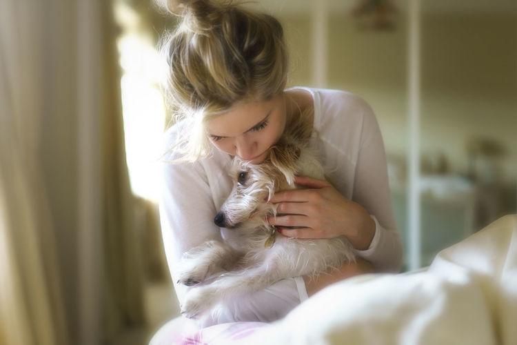 Young woman cuddling dog at home