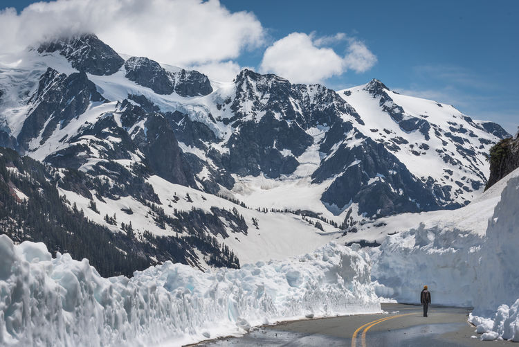 Rear view of person on road by snowcapped mountain against sky