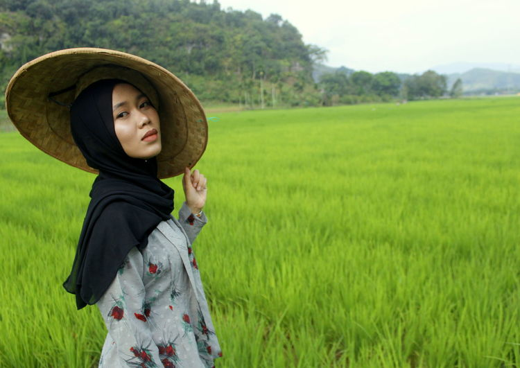 Portrait of woman in asian style conical hat standing on field