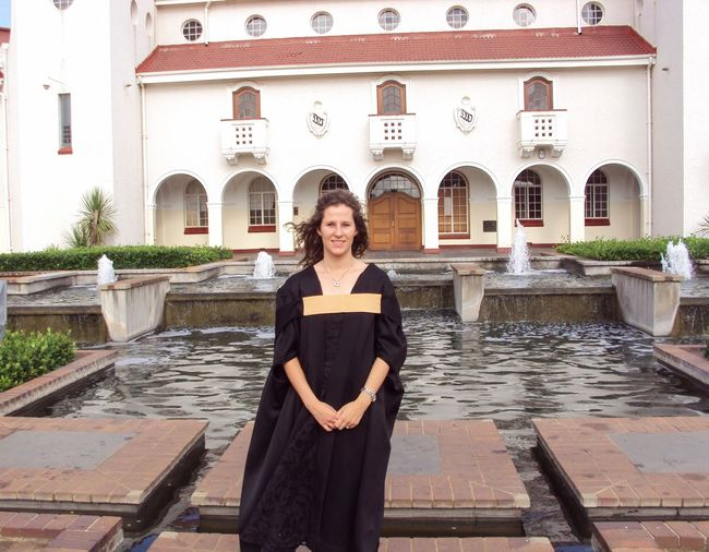 Woman wearing graduation gown standing by pond against building