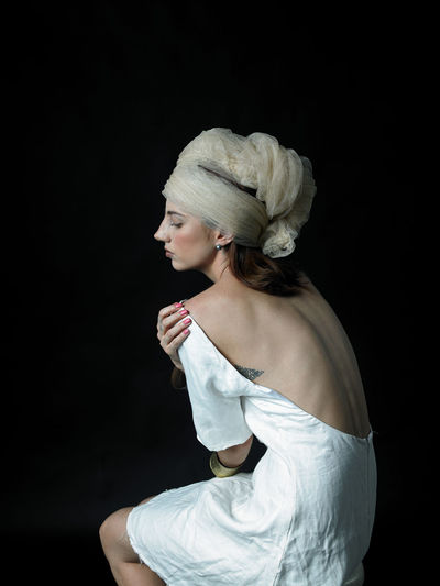 Side view of young woman sitting against black background
