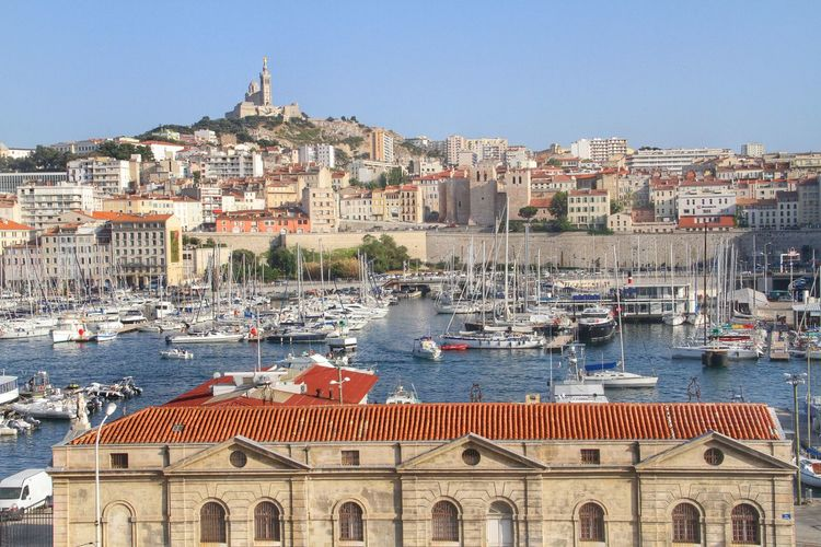 Sailing boats at harbor and church notre-dame de la garde in background