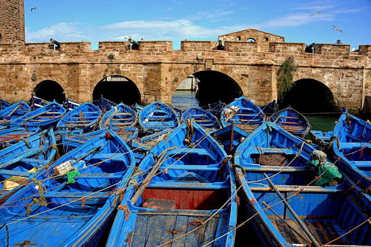 Boats moored against bridge