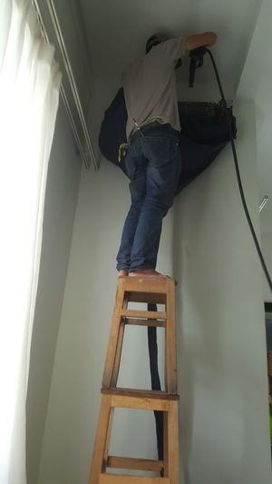 Balancing act ... air-conditioning technician balances on two stools in Vietnam. Standing Indoors  Repairing Balance Workers Stools Airconditioning Technicians Vietnam Da Nang Riverside Đà Nẵng