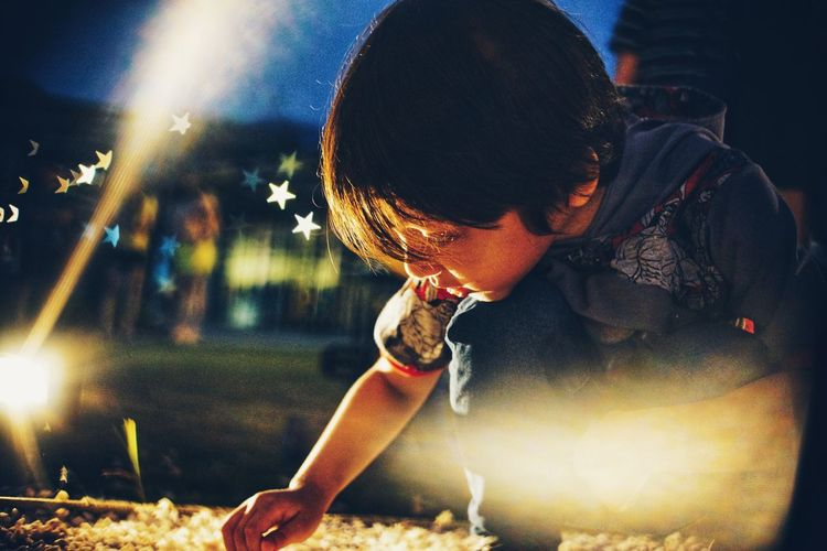 Digital Composite Image Of Boy Crouching While Playing Outdoors At Night