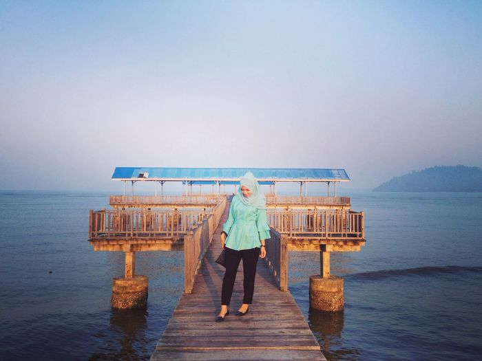 Woman standing on pier over sea against clear sky