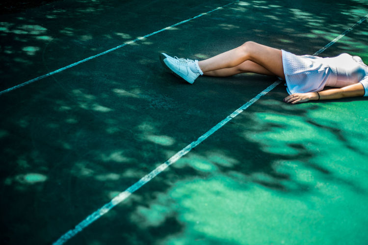 Low section of young woman lying on tennis court