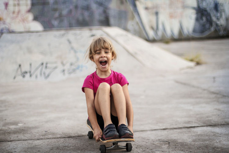 Girl having fun skateboarding in skatepark on sunny day Casual Clothing Child Childhood Day Emotion Females Front View Full Length Girls Innocence Leisure Activity Lifestyles Mouth Mouth Open One Person Outdoors Real People Sitting Summer Sports