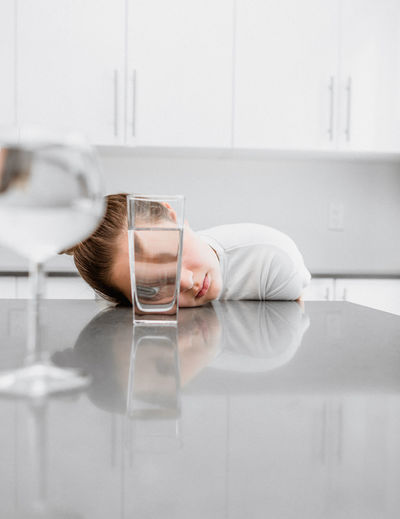 Reflection of man drinking water in glass on table