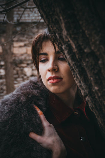 Close-up of thoughtful woman by tree
