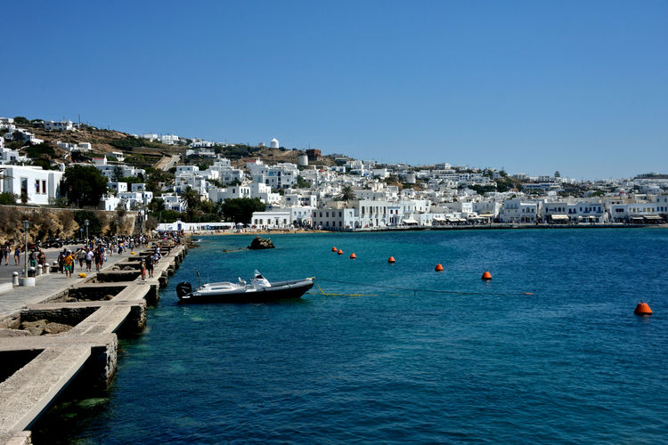 panoramic seaside view of Mykonos with white buildings and moored boat Water Nautical Vessel Transportation Architecture Building Exterior Sky Sea Mode Of Transportation Built Structure Day City Blue Travel Nature Travel Destinations Clear Sky Group Of People Tourism Building Outdoors Cityscape Mykonos,Greece Seascape Boat Cityscape Port Harbour Pier High Angle View Summertime Travel Panorama Panoramic View