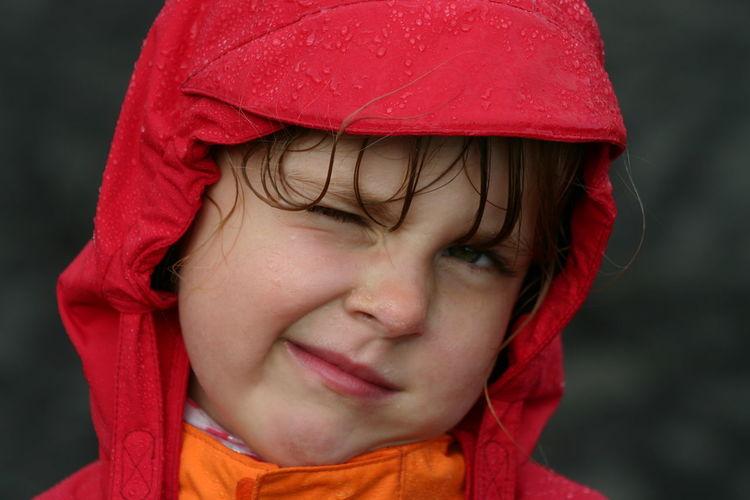 Close-up portrait of girl wearing raincoat winking eye