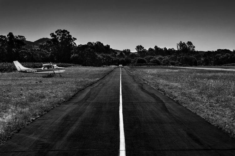 Biplane by runway against clear sky
