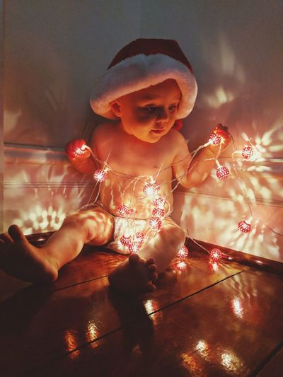 Close-Up Of Cute Baby With Illuminated Lights On Floor At Home