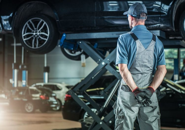 Rear view of mechanic at auto repair shop