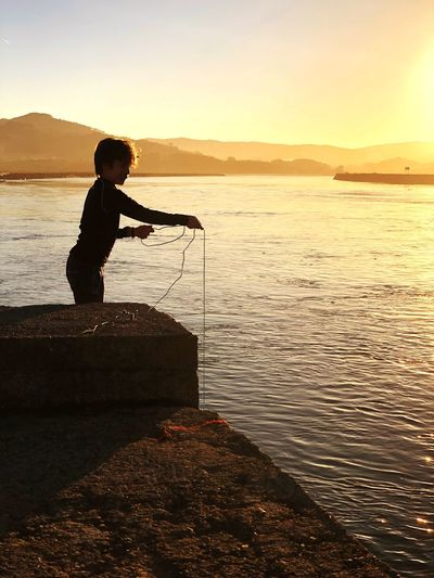 Fishing Sunset Water Silhouette Real People One Person Nature Sea Beauty In Nature Leisure Activity Scenics Tranquil Scene Standing Men Tranquility Rock - Object Outdoors Mountain Side View Sky Full Length