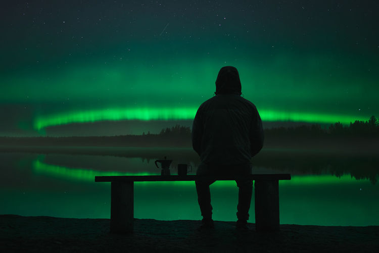 A man sits on a bench near the lake and looks at the northern lights. Coffee maker and mug nearby on the bench Night Sitting One Person Seat Green Color Beauty In Nature Leisure Activity Star - Space Astronomy Water Space Sky Men Lifestyles Lake Aurora Polar Lights Silhouette Bench Magnetic Storm North Russia Finland Sweden