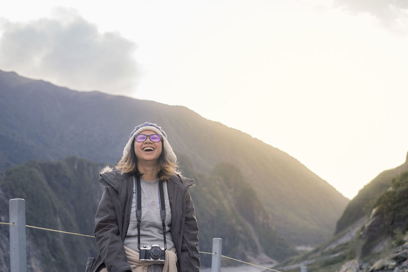 Happy Woman Carrying Camera While Standing Against Mountain During Foggy Weather