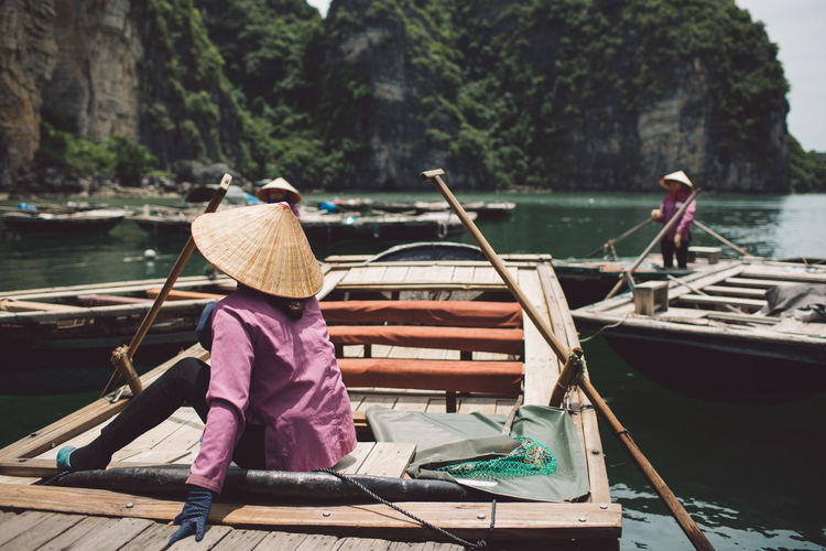 Rear View Of Woman Wearing Asian Style Conical Hat While Sitting On Rowboat At Halong Bay