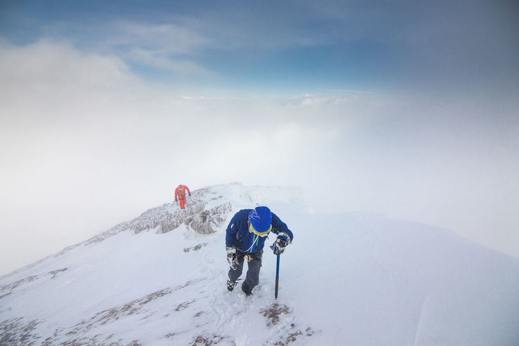 Hikers walking on snow covered mountains against sky