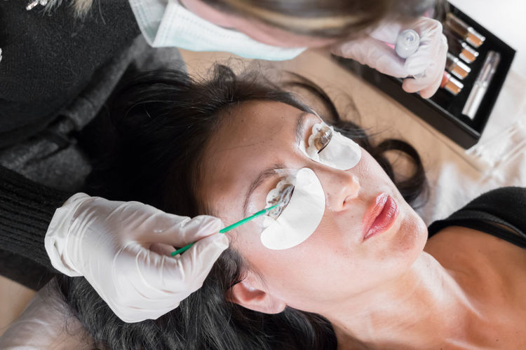 High angle view of beautician applying beauty product on woman face