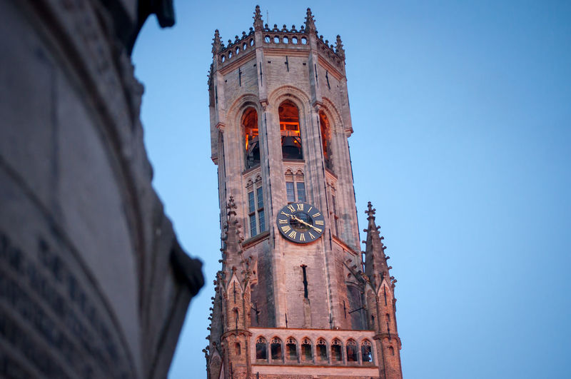 Low angle view of clock tower against clear sky at dusk
