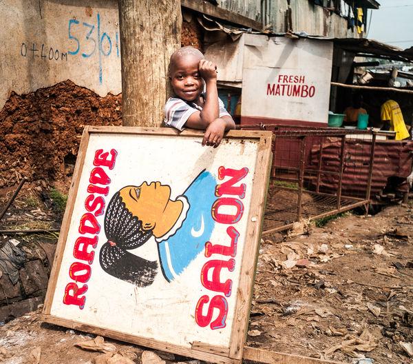 Small Business 3rdworld Kenya Nairobi Jua Kali Life In A Slum Kibera Slum KiberaStories Kibera Childhood Text Portrait Looking At Camera Child Roadside Hairsalon Salon Real Life Sign Innocence