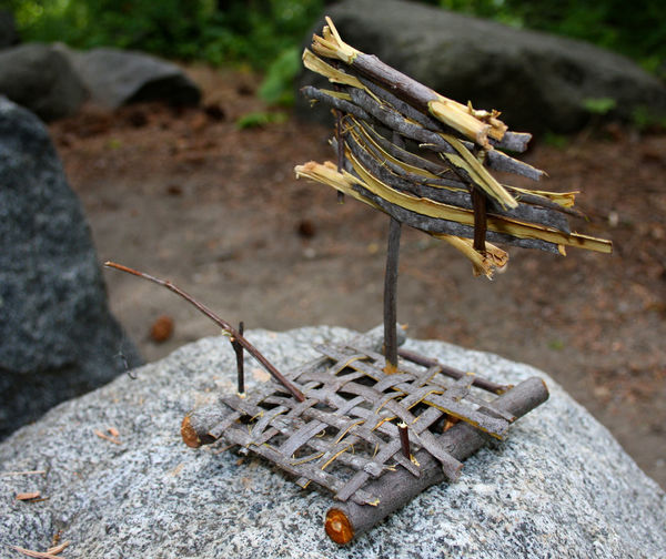 Close-up of wooden toy raft on rock
