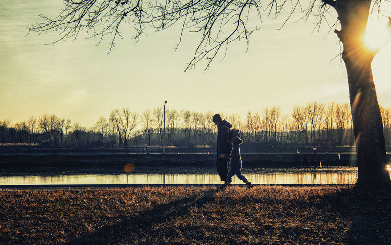 Side view of man walking by lake against sky during sunset