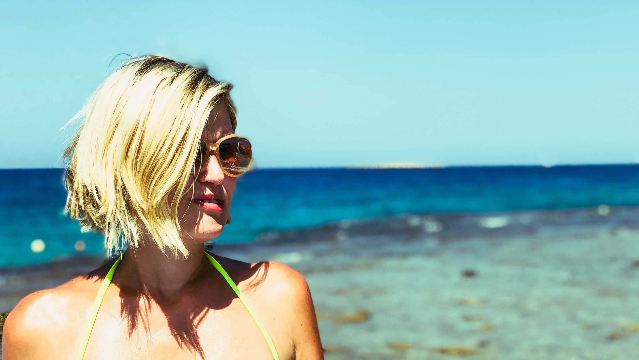 sea, headshot, water, blond hair, sky, beach, portrait, real people, one person, lifestyles, hair, nature, horizon over water, land, leisure activity, horizon, sunlight, young adult, hairstyle, outdoors