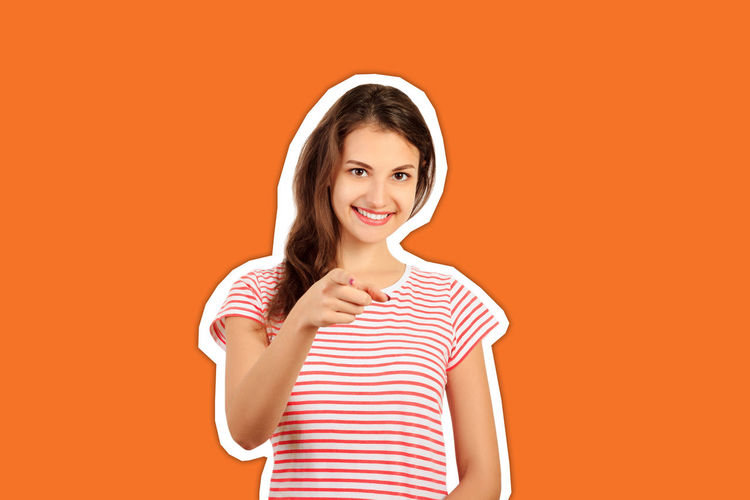 Portrait of smiling young woman against orange background