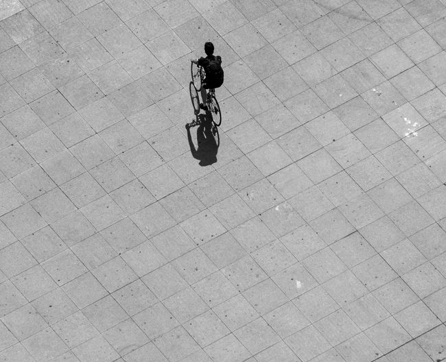 High Angle View Of Man Riding Bicycle On Footpath