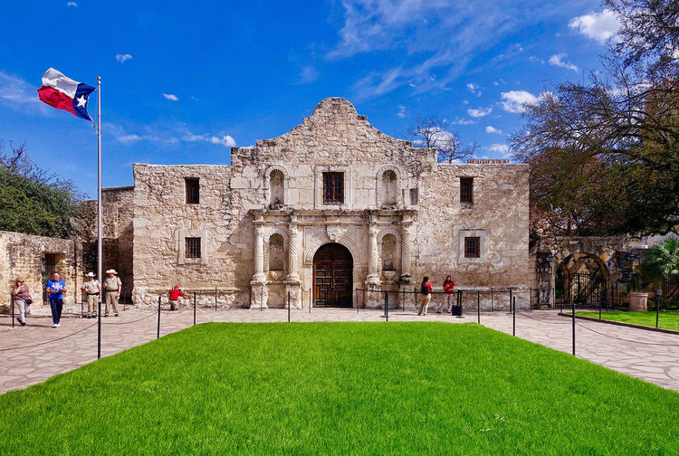 The Alamo in San Antonio in the USA. Church Grass Mission San Antonio Texas USA Architecture Army Barracks Building Exterior Built Structure Clouds Day Flag History Meadow Museum Outdoors People Place Of Wars Sly The Almamo Travel Destinations Tree