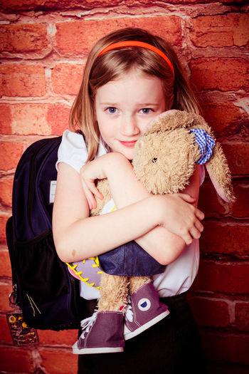 Portrait Of Schoolgirl Embracing Stuffed Toy Against Brick Wall