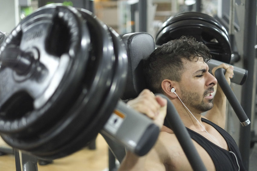 Man training in gym and posing showing muscles 25 Years Old Effort GymLife Headphones Latin Man Profile Shoulder Spanish Day Exercise Equipment Exercising Fitness Gym Health Club Indoors  Lifestyles Men Muscle One Man Only One Person Pectoral Training Weights Young Adult