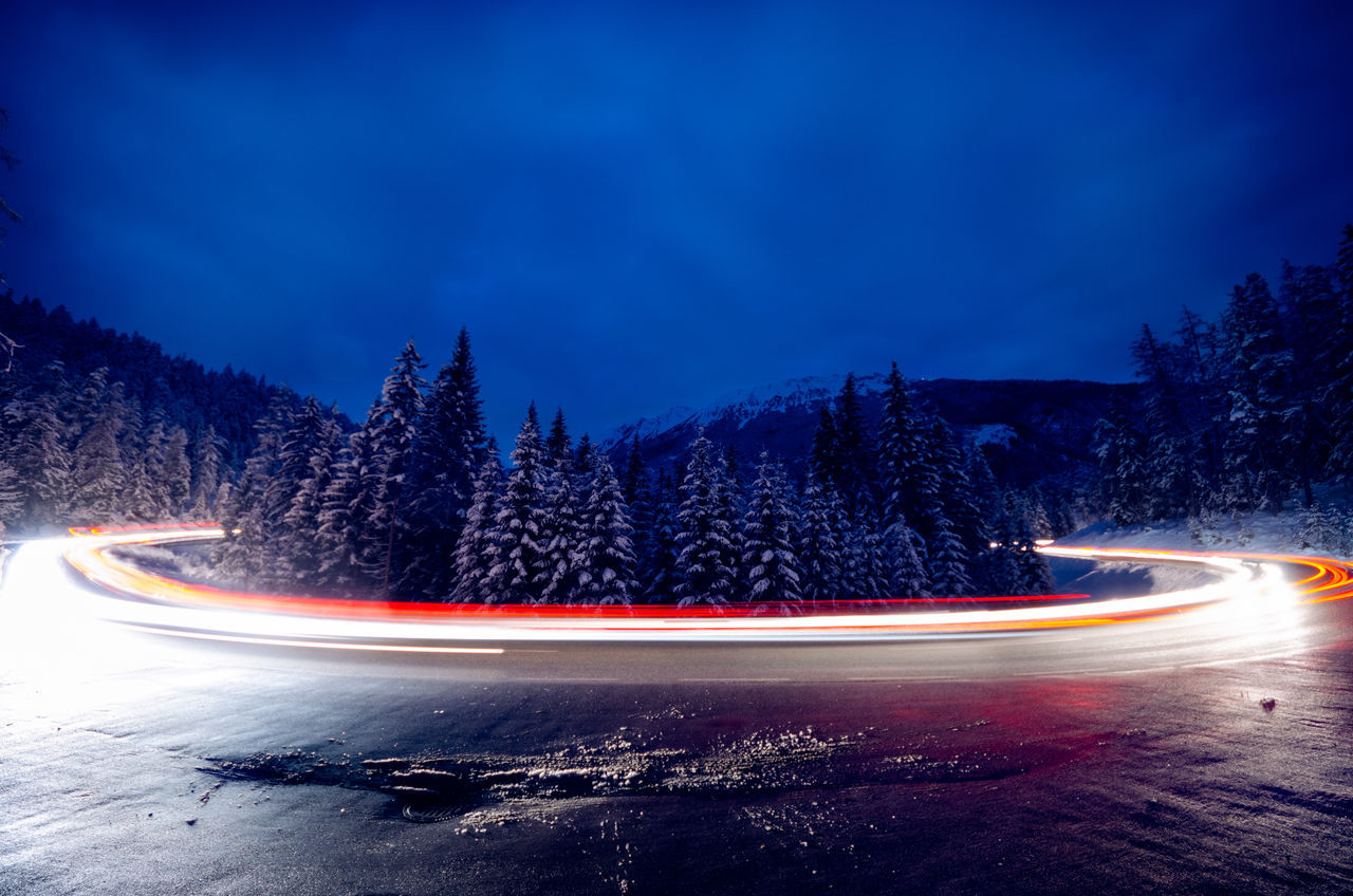 Light trails on road against sky at dusk during winter