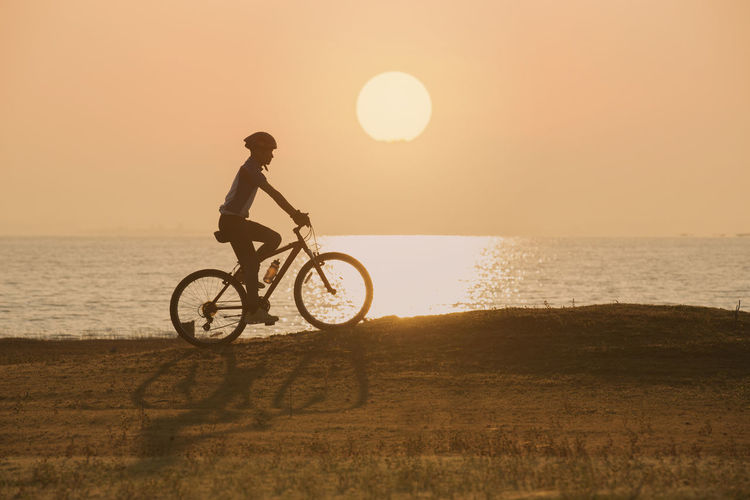 silhouette of cyclist on sunset or sunrise sky background Sky Sunset Bicycle Sea Water Sun Land Transportation Beauty In Nature Horizon Over Water One Person Nature Ride Riding Leisure Activity Lifestyles Sunlight Horizon Beach Outdoors Lens Flare